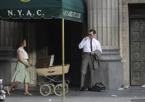 Don Draper stands outside the New York Athletic Club, observing a passerby.
